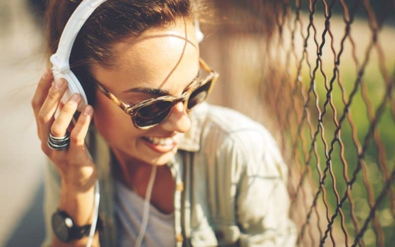Woman smiling and listening to happy music on headphones