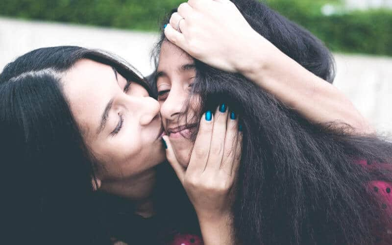 Mother kissing teenage daughter's cheek