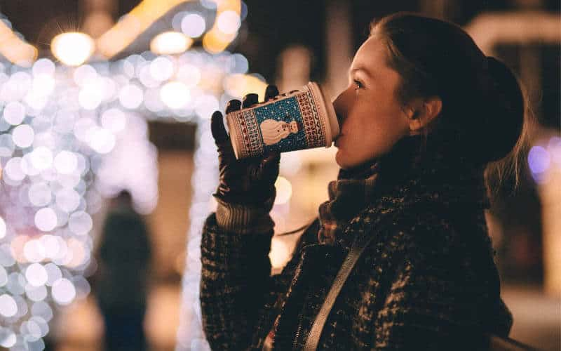Woman drinking coffee outside at Christmas market