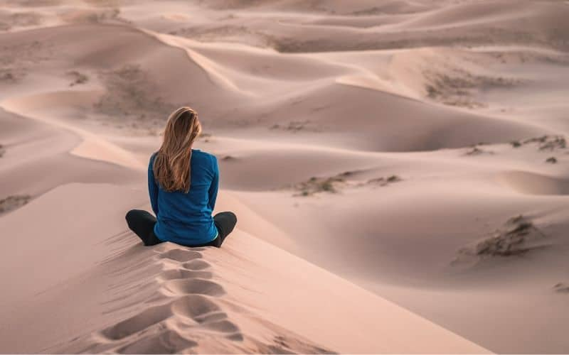 Woman sitting on the board on a sand dune